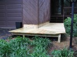 Floating deck level with steps with drainage between wall – by DeckResurrect